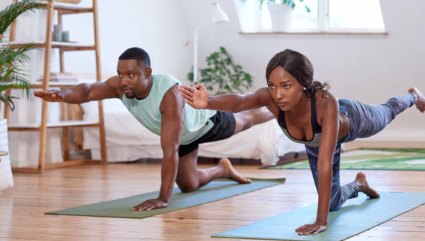 Young attractive black couple practising yoga in their trendy apartment