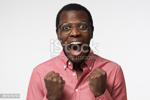 613525808 istock photo Young attractive black male in glasses shouting while his team win, raised both fist in victory gesture, isolated on gray background 997616750