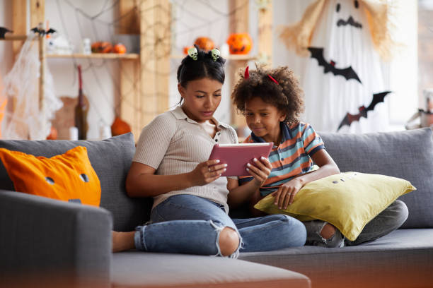 Young attractive black mother sitting on sofa in living room and using tablet while reading Halloween story to son stock photo