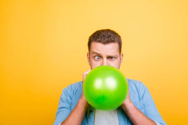 attraktive blonde jüngling müde zu sprengen luftballons silvesterparty, verdrehte augen auf gelbem hintergrund - ballonhose stock-fotos und bilder