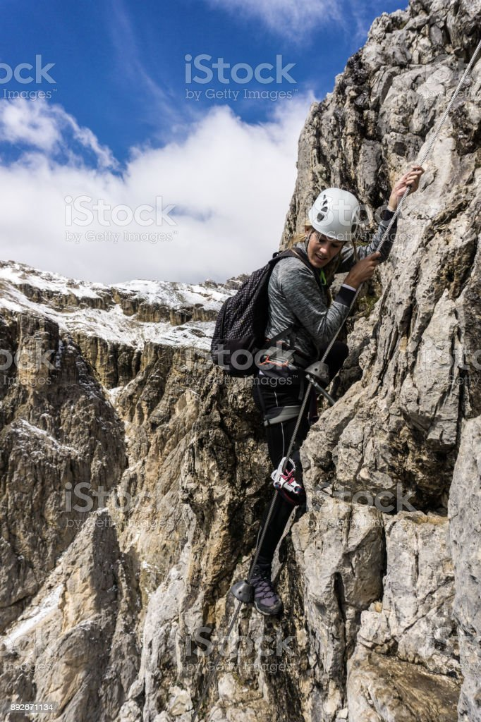 young attractive blonde female climber on a Via Ferrata in the Dolomites stock photo