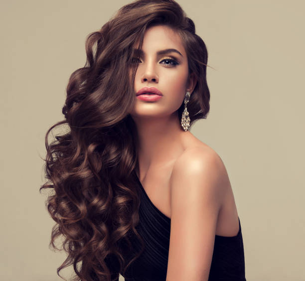 Young attractive brunette with voluminous, shiny and curly hairstyle. Young woman brunette with voluminous, shiny and wavy hair . Beautiful model with long, dense and curly hairstyle. Frizzy hair. long hair stock pictures, royalty-free photos & images