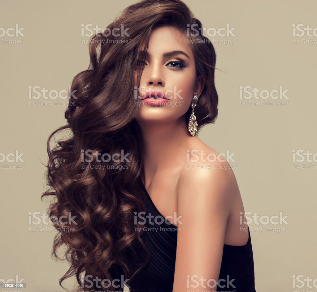 Young attractive brunette with voluminous, shiny and curly hairstyle. stock photo