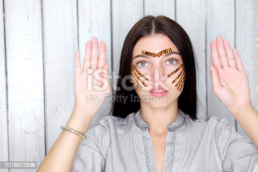 istock Young attractive brunette woman with tiger colored tapes after taping face procedure in beauty parlor show opened hands 1016672696