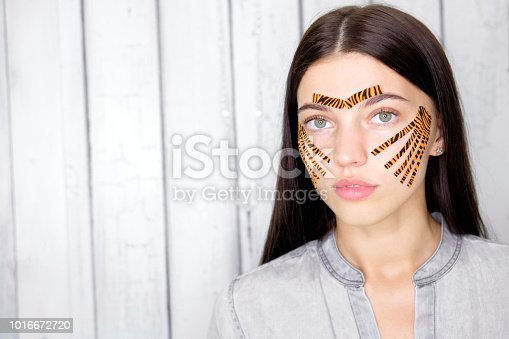 istock Young attractive brunette woman with tiger colored tapes after taping face procedure in beauty parlor 1016672720
