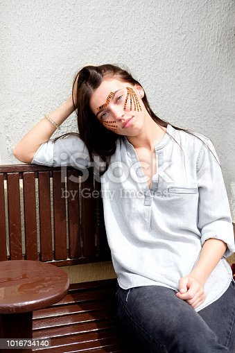 istock Young attractive brunette woman with tiger colored tapes after taping face procedure in beauty parlor sitting in street 1016734140