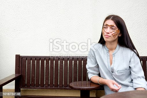 istock Young attractive brunette woman with tiger colored tapes after taping face procedure in beauty parlor sitting in street 1016734146