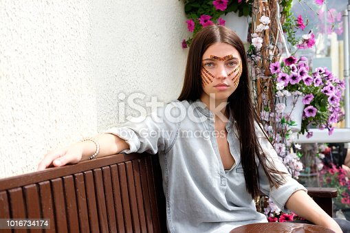 istock Young attractive brunette woman with tiger colored tapes after taping face procedure in beauty parlor sitting in street 1016734174