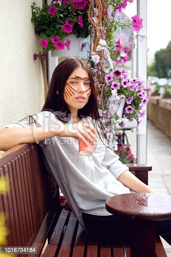 istock Young attractive brunette woman with tiger colored tapes after taping face procedure in beauty parlor sitting in street 1016734184