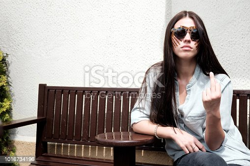 istock Young attractive brunette woman with tiger colored tapes after taping face procedure in beauty parlor sitting in street 1016734196