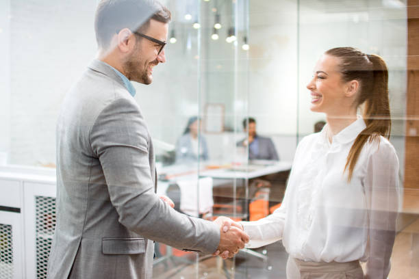Young attractive business woman and handsome businessman shaking hands indoors. stock photo