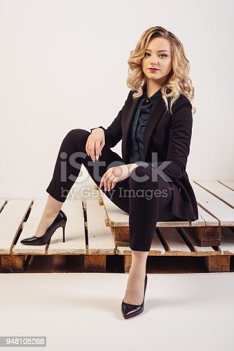 istock Young attractive business woman in expensive suit and shoes sits on painted pallets 948105268