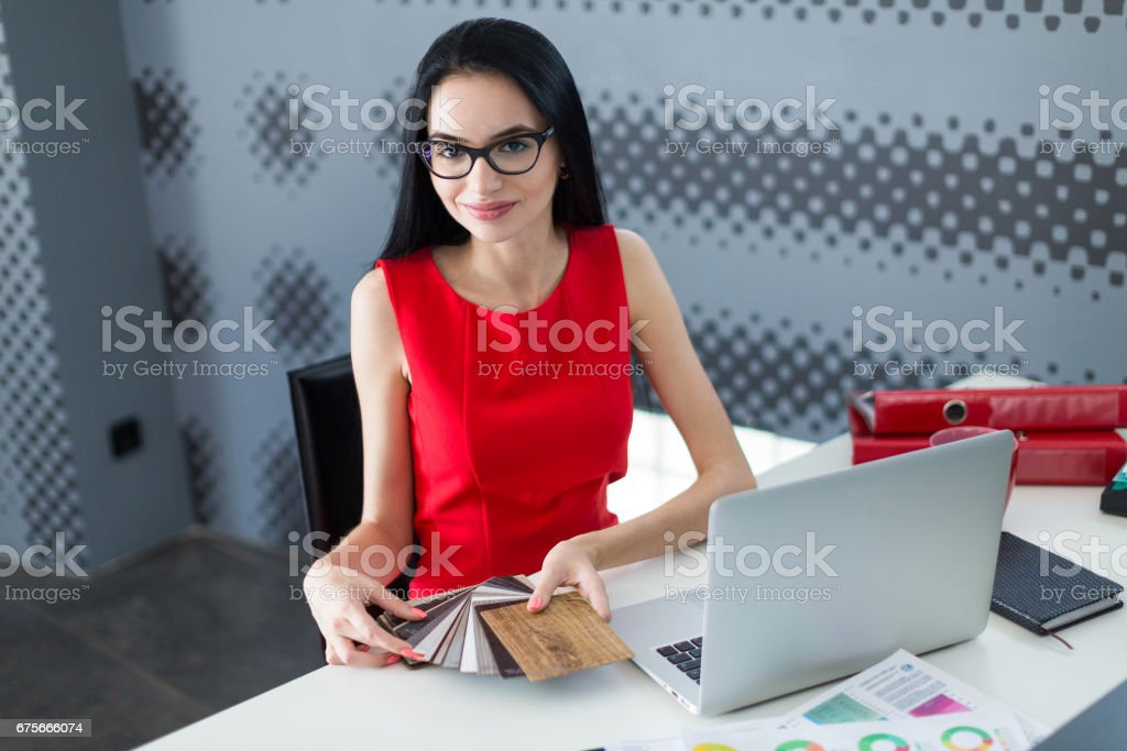 Young attractive businesslady in red dress and glasses sit at the table and work with laptop and hold wood samples royalty-free stock photo