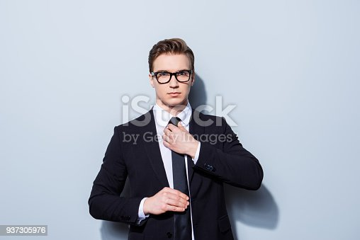 973213156 istock photo Young attractive businessman banker is standing on the pure light background. He looks stunning! So severe and confident, in tuxedo and glasses 937305976