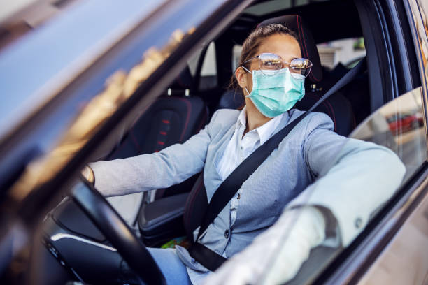 Young attractive businesswoman dressed smart casual with protective mask and gloves on sitting in her car and she is ready to drive it. Protection from corona virus concept. stock photo