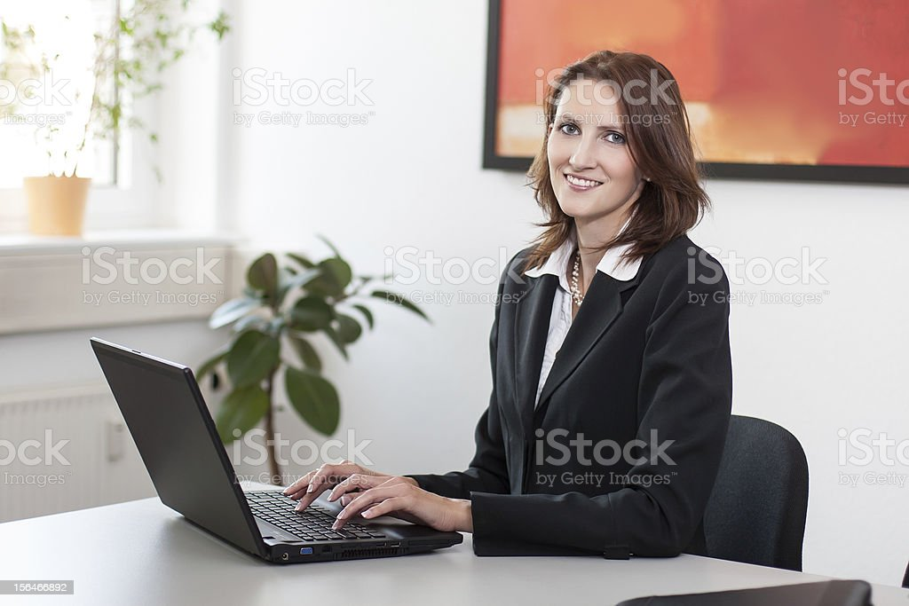 Young attractive businesswoman uses her laptop royalty-free stock photo