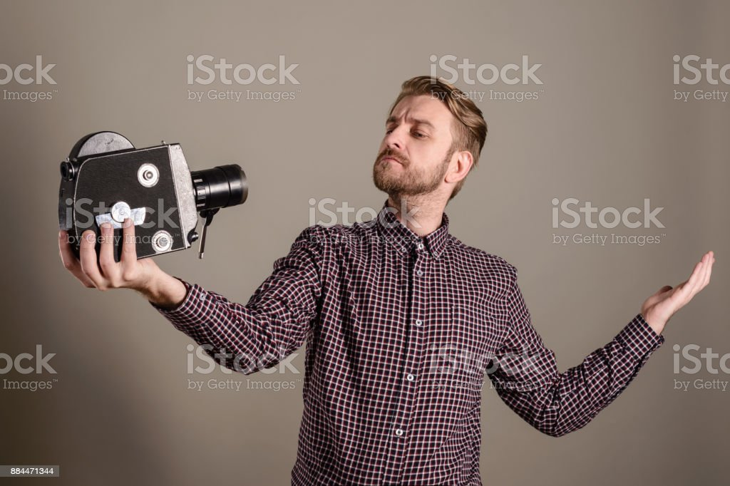 Young attractive cameraman in a plaid shirt takes himself off to an old movie camera. Selffi concept stock photo