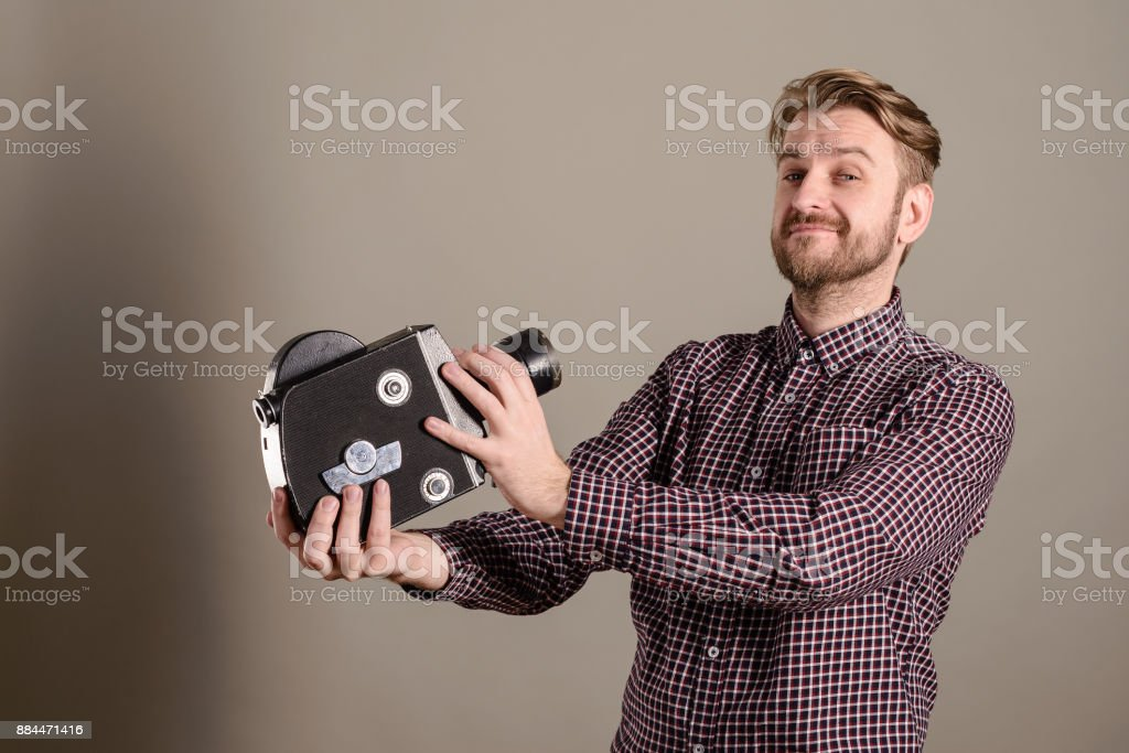 Young attractive cameraman in a plaid shirt takes himself off to an old movie camera stock photo