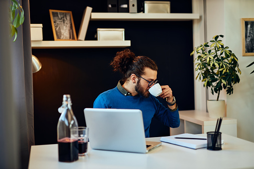 530281733 istock photo Young attractive caucasian bearded freelancer sitting at his home office and drinking morning coffee. On table is laptop. 1195618138