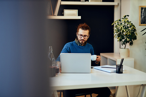 530281733 istock photo Young attractive caucasian bearded freelancer sitting at his home office and drinking morning coffee. On table is laptop. 1203196170