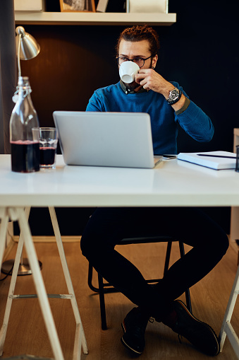 530281733 istock photo Young attractive caucasian bearded freelancer sitting at his home office and drinking morning coffee. On table is laptop. 1203202890