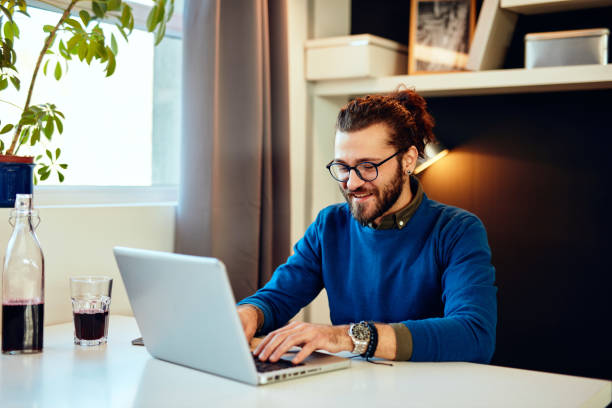 Young attractive Caucasian hipster sitting in office and typing on laptop. stock photo