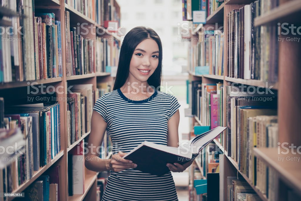 Young attractive clever successful asian female student is holding big thesaurus in hard bookcase, wearing casual striped t shirt, behind her are book shelves of campus library stock photo