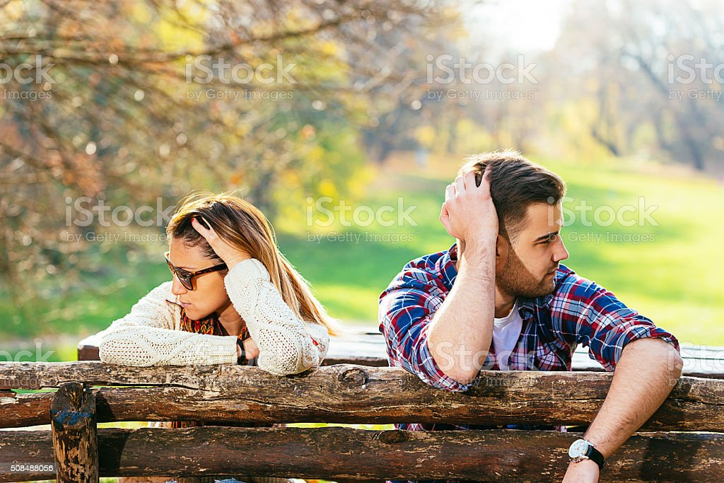 Young attractive couple having relationship issues in park stock photo