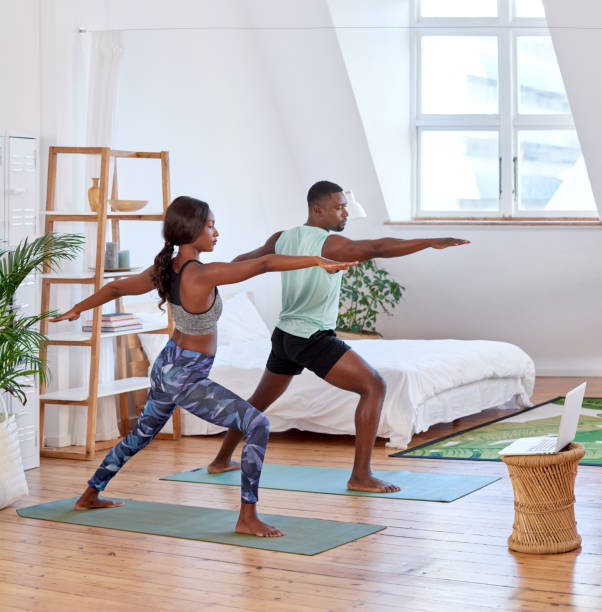 Young attractive couple practising yoga at home