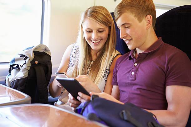 junges paar reading e buchen sie auf der zugfahrt - schnell lesen lernen stock-fotos und bilder