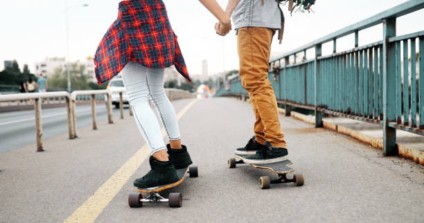Young attractive couple riding skateboards and having fun stock photo