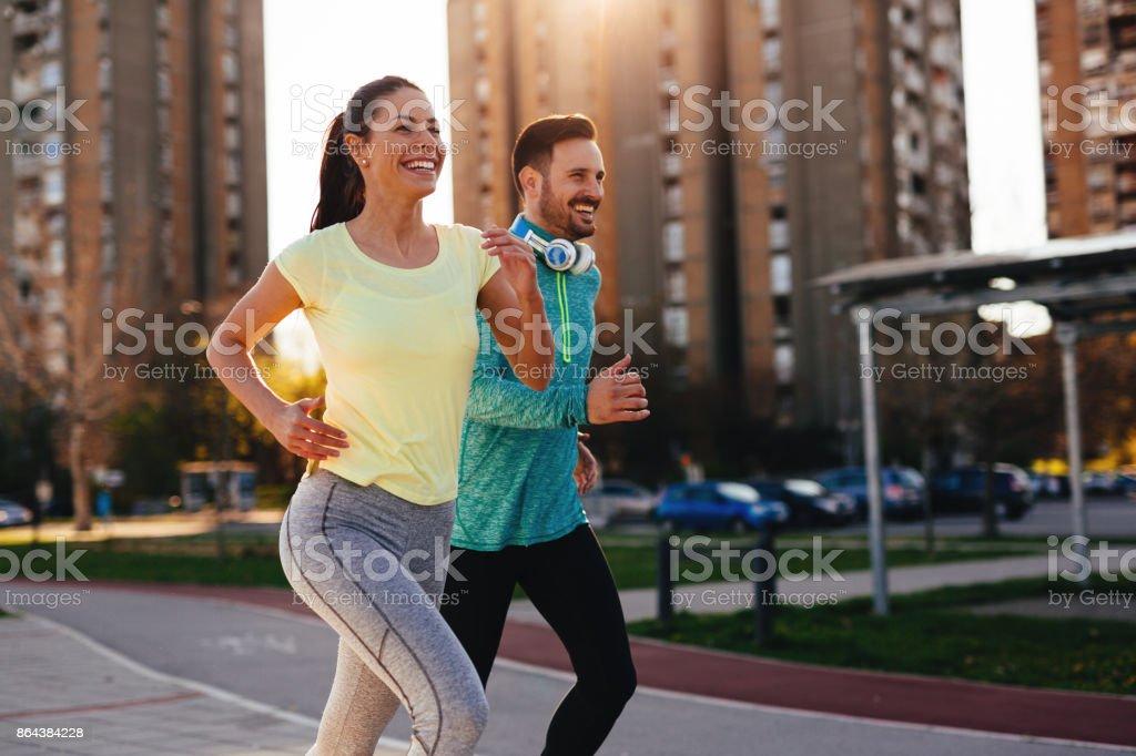 Young attractive couple running outside on sunny day - Foto stock royalty-free di Abbigliamento sportivo