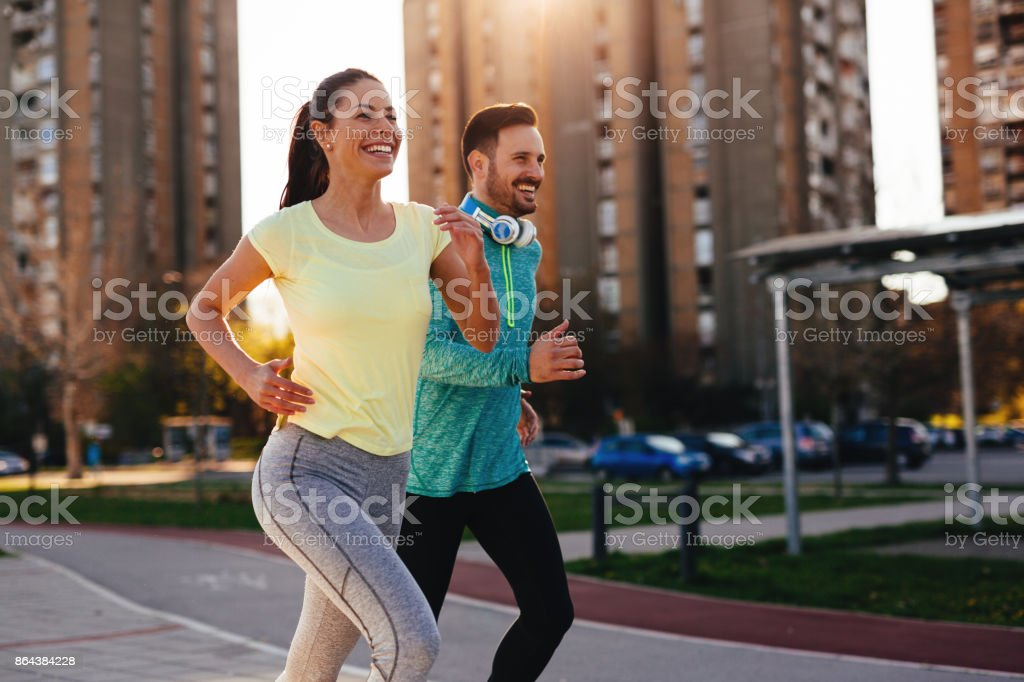 Young attractive couple running outside on sunny day stock photo