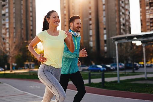 Young Attractive Couple Running Outside On Sunny Day - Fotografie stock e altre immagini di Abbigliamento sportivo