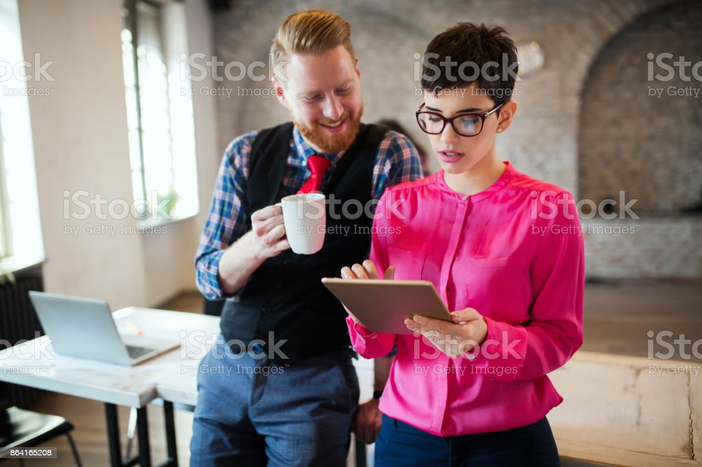Young attractive designers talking and looking at digital tablet royalty-free stock photo