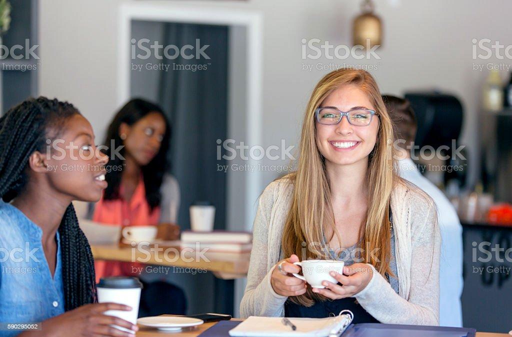 Young attractive diverse female friends in a coffee royaltyfri bildbanksbilder