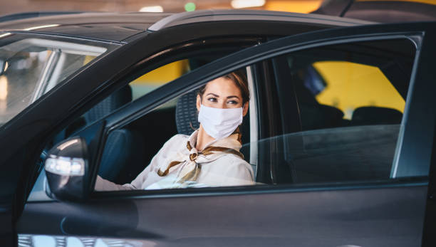 Young attractive elegant businesswoman with protective face mask on exiting car during corona virus outbreak. stock photo