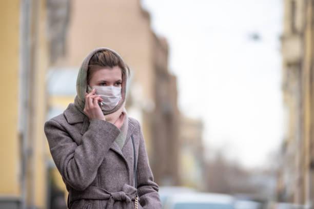 Jovem mulher branca européia atraente em uma máscara de proteção médica contra vírus da gripe e coronavírus COVID-19 falando ao telefone em uma rua da cidade - foto de acervo
