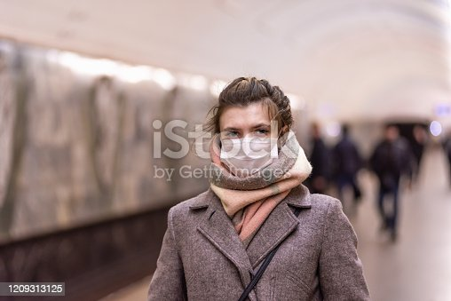 Young attractive European Caucasian woman in a protective mask protecting against influenza viruses and coronavirus COVID-19 in the subway