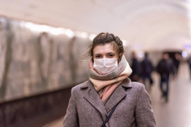 ung attraktiv europeisk kaukasisk kvinna i en skyddande mask som skyddar mot influensavirus och coronavirus covid-19 i i tunnelbanan - cold street bildbanksfoton och bilder