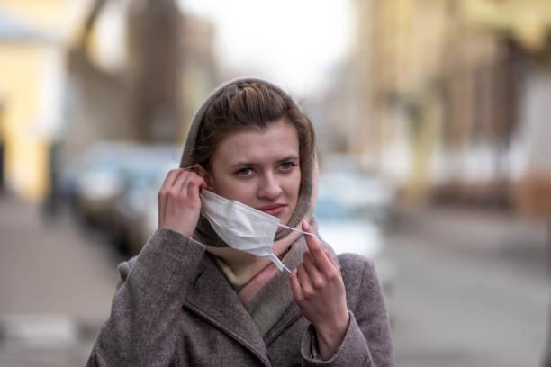 Jovem mulher branca européia atraente fora de sua máscara protetora contra o vírus da gripe e coronavírus COVID-19. - foto de acervo