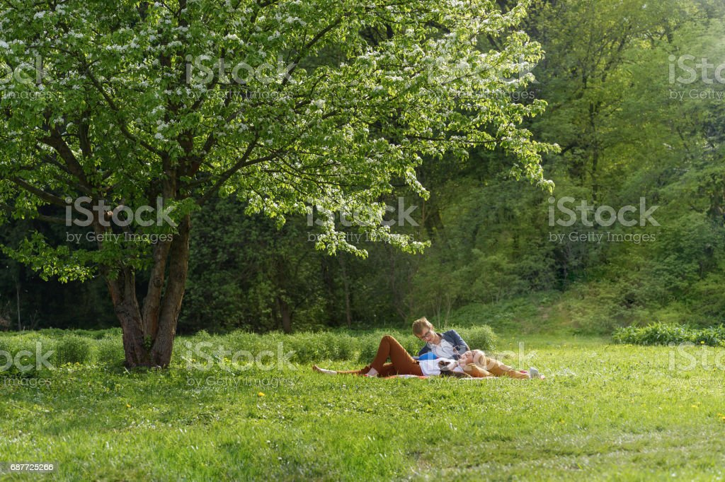 young attractive european couple with small dog is getting rest on blanket in some summer park at warm sunny day. Beautiful woman put her head to knees of husband. stock photo