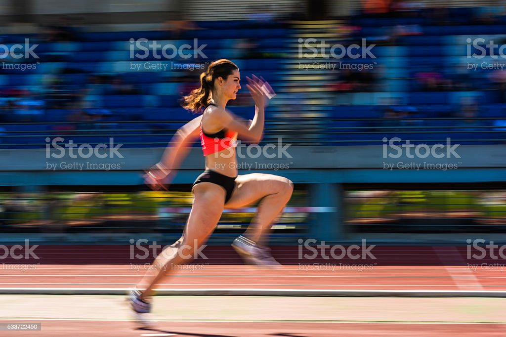 Young attractive female athlete at long jump, pannig shot stock photo