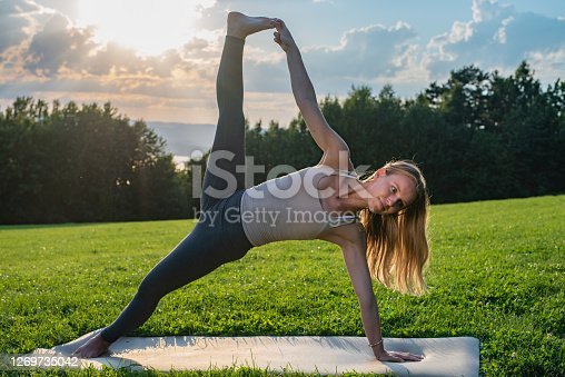 Young yogi woman in Side Plank pose outdoors.