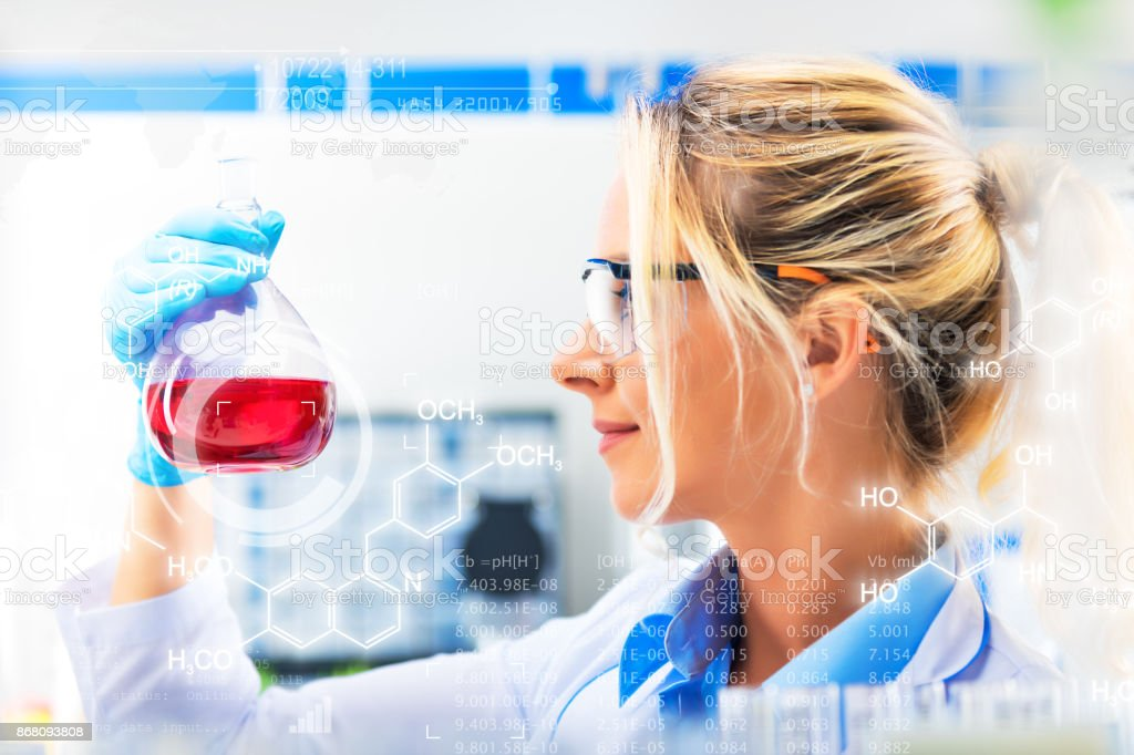Young attractive female scientist holding a flask with red liquid substance in the laboratory stock photo