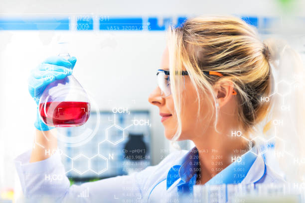 研究室で赤い液体物質とフラスコを保持若い魅力的な女性科学者 ストックフォト