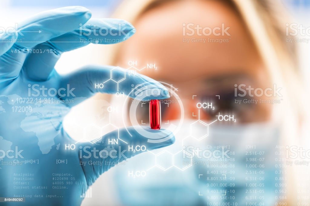 Young attractive female scientist holding a red transparent pill stock photo
