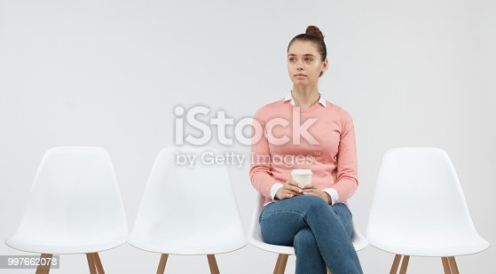 istock Young attractive female sitting on the white chair at the line to visit doctor in medical clinic. Copy space for advertising text. 997662078