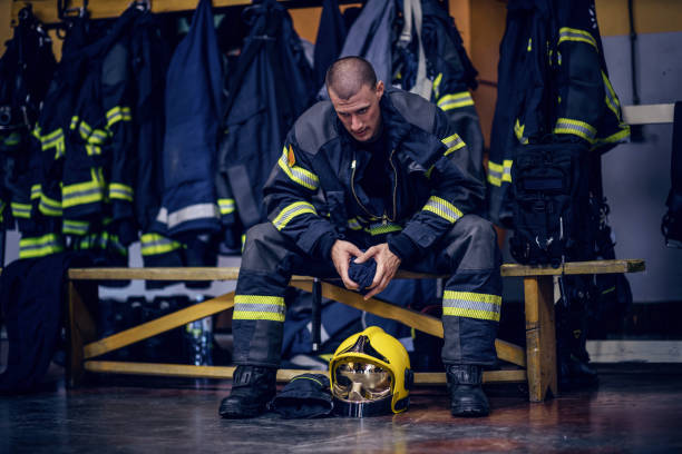 Young attractive fireman in protective uniform sitting in fire station and waiting for other firemen. He is prepared for action. stock photo