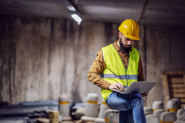 Young attractive focused bearded supervisor in vest with helmet on head standing inside of underground parking lot in construction process and using laptop. stock photo